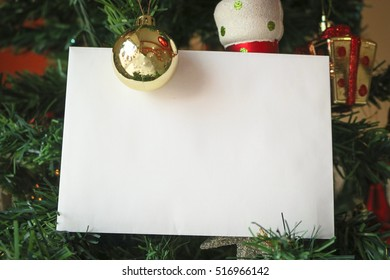 Christmas template background with blank white greeting card for invitation letter or inbound email marketing surrounded by holiday decorations. Concept Image.