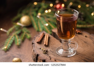 Christmas and Thanksgiving mulled apple cider with spices: cinnamon sticks, cloves, anise on white table with traditional rustic Christmas background flowers arrangement, Autumn and winter drink.