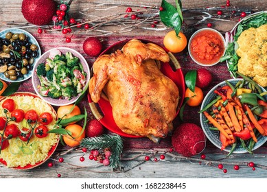 Christmas or Thanksgiving whole roasted chicken, rice, pumpkin, corn, honey, nuts, vegetable salads over wooden background. Top view, copy space. Autumn harvest, organic vegetables. Autumn family