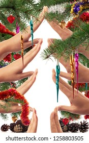 Christmas themed concept of hands making a Christmas tree shape framed with branches and colorful ornaments on white background