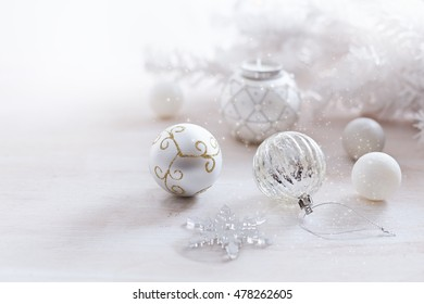 Christmas themed ornaments in silver and white over white background