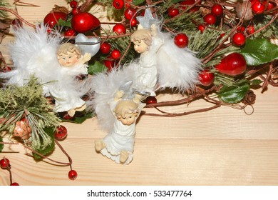 Christmas three angels on the background of fir branches with berries