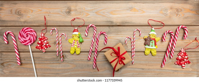Christmas time. Candy canes, christmas ornaments and a gift box with red ribbon on wooden background, banner, top view