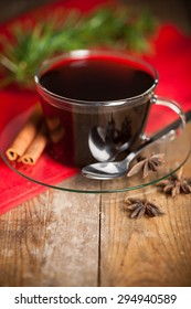 Christmas time, cup of tea with cinnamon and anise spices, festive decoration and candles on wood background.