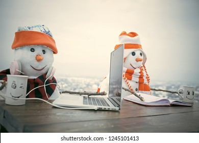 Christmas time and education, fairytale. New year snowman from snow in hat read book. Snowman in winter drink hot wine from tea cup. Happy holiday celebration. Xmas or christmas decoration, audio book