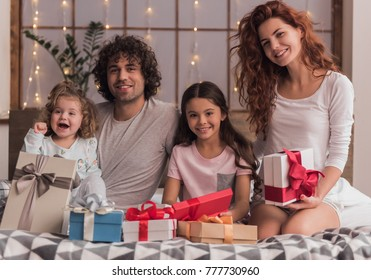 It's Christmas time! Happy parents and their daughters are opening the presents, looking at camera and smiling while sitting in bed at home