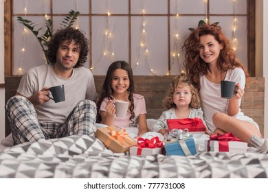 It's Christmas time! Happy parents and their daughters are holding cups and smiling while sitting on bed with presents