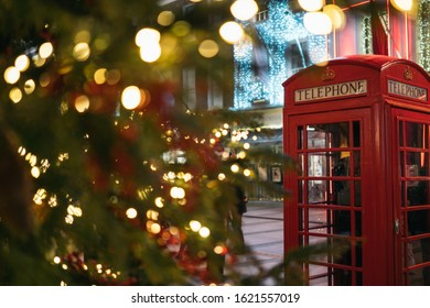 Christmas time in London: a red telephone booth in front of an illuminated Christmas Tree in Central London, UK, during night time