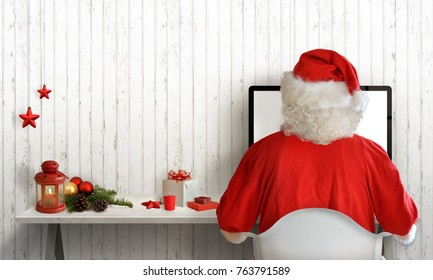 Christmas time in Santa Claus room. Santa answers letters on the computer. Free space for greeting text. White wooden wall in background.