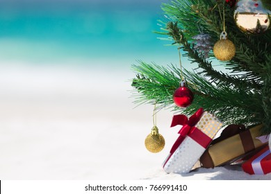 Christmas time spent at the beach in summer. A christmas tree surrounded by presents on a beautiful sandy beach.  Shallow dof with space for copy