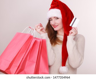 Christmas time. Young latin woman wearing santa claus hat holding red shopping bags and credit card, buying gifts