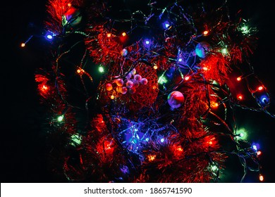 Christmas tiny lights playing in all colors on a black background. Abstract art. Christmas bulbs. The light bulbs on the wire intertwine. Red, blue, green nad more shadows of colors.
