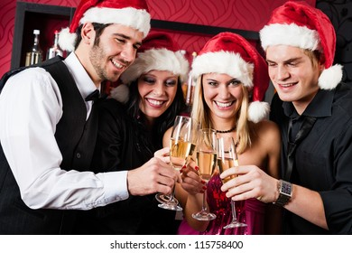 Christmas toasting party cheerful young friends with champagne at bar