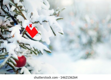 Christmas Tonga. Xmas tree covered with snow, decorations and a flag of Tonga. Snowy forest background in winter. Christmas greeting card.
