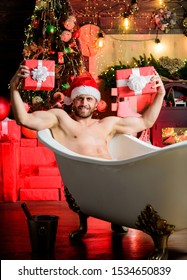 Christmas tour concept. Man lying in bathtub with gift box. Sexy hedonist relax in bathtub. Stunning winter views enjoyed from bathtub. Enjoy New Years Eve celebrations book stay hotel apartment.