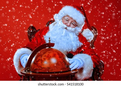 Christmas, tourist trip concept. Santa Claus sitting on his armchair and making plans of travelling around the planet. Christmas time. Time for miracles. Copy space.