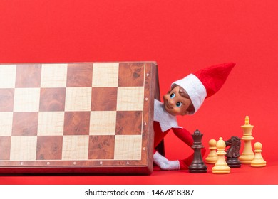 Christmas toy dwarf elf hiding under chess board. Funny Xmas activities for family