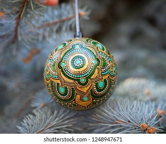 Christmas toy. Green ethnic painted new year ball on pine brunch. Holiday collection