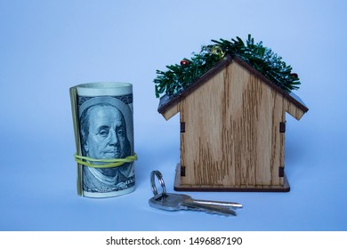 Christmas toy house with keys on a white background and dollars. Buying a home. Winter Christmas concept New Year warm cozy loving home protection. copyspace