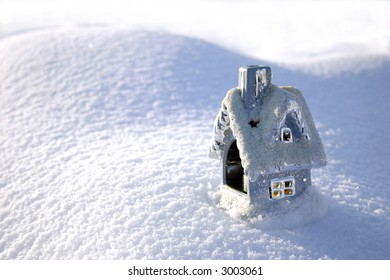 Christmas toy house on the snowdrift and sun shadows