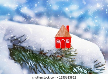 Christmas toy house on winter background. Concept of winter, Christmas and new year, warm and cozy, loving, protecting. toy house in snow. soft selective focus, close up