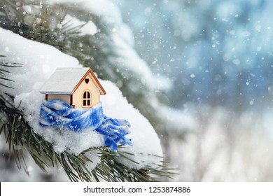 Christmas toy house in scarf, on winter snowy background. winter season concept. Christmas and new year holiday. mini wooden house in snow. copy space