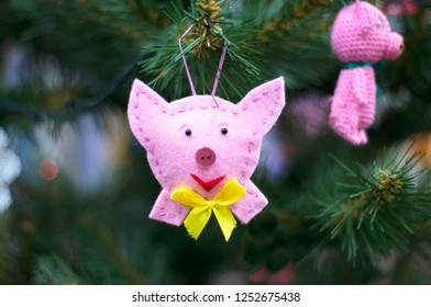 Christmas toy pig hanging on a Christmas tree branch
