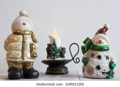 Christmas toy snowman on a light background with decorative candles. Christmas horizontal composition. Christmas decorations. New Year's holiday composition. postcard.