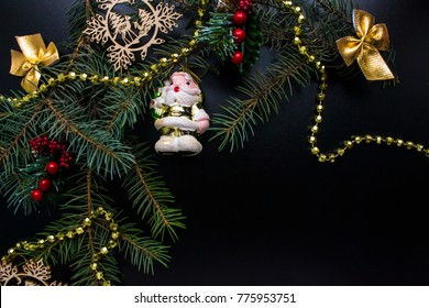 Christmas toy with sprigs of fir on a black background