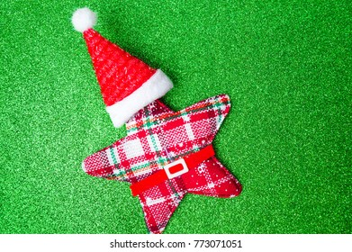 Christmas toy star with Santa hat on green glitter background
