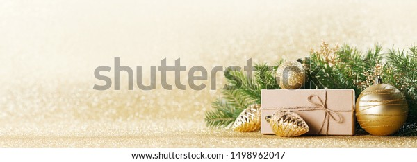 Christmas toys, decorations, present gift box wrapped in kraft paper on golden glitter background, copy space