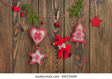 Christmas toys (deer, christmas tree, heart, star) hanging over wooden background.