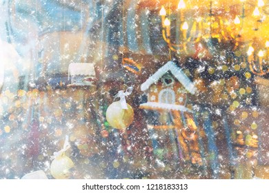 Christmas toys in the form of balls and small houses on ropes for the glass of the shop window curved in the Old City