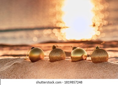 Christmas toys - golden balls on the beach, blurred sea in sunset light in the background. New Year or Christmas card, invitation with copy space for text