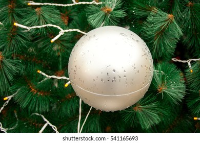 Christmas toys are on the Christmas tree. New year background, it's glass ball and tree branches