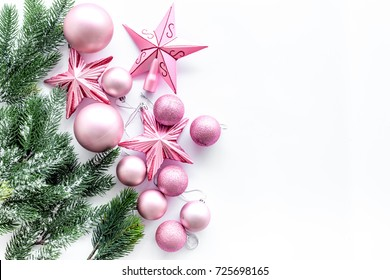 Christmas toys pattern. Pink stars and balls near pine branches on white background top view copyspace