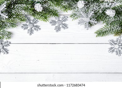 Christmas toys and spruce branches on wooden background top view
