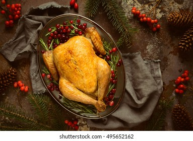 Christmas traditional dish, roasted chicken in an oval dish decorated in a rustic style according to season, dark moody stylized photo, view from above