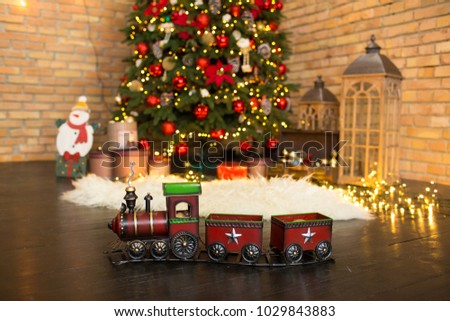 christmas train and a tree with decorations at the background
