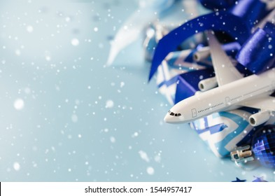 Christmas travel planning. Traveling as gift. White blank model of passenger plane, passports and gift boxes on blue background. Copy Space. Snow effect.