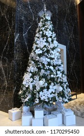 Christmas tree with all white decorative ornaments and snowflakes erected against black granite wall. Under the tree are white decorative presents and boxes with white ribbons.