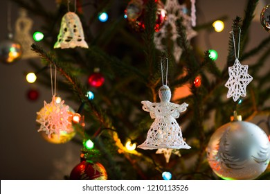 Christmas tree with angel shape crochet ornament, baubles and lights.