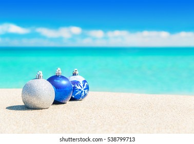 Christmas tree balls decorations on the sand of tropical ocean beach - happy New Year and Merry Christmas holidays travel destinations in hot countries concept