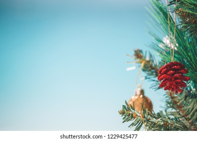 Christmas tree and baubles on the beach background.   Out of focus background of aqua blue s beach waves.  Space for copy