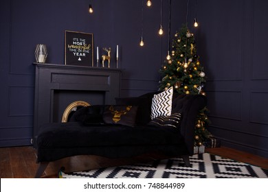 Christmas tree black and gold with gifts near it in beautiful interior room