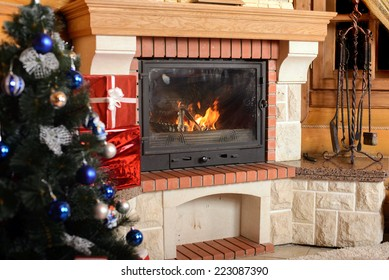Christmas tree and boxes with gifts for family, fireplace background.