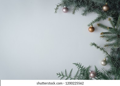 Christmas tree branch with colorful baubles decoration. Minimal creative flat lay. New Year Christmas background concept.
