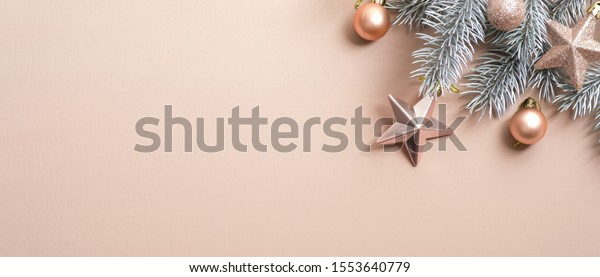 Christmas tree branch with cream color balls and stars on copper background. Flat lay, top view, copy space. Minimal style Xmas composition. Christmas party greeting card template, New Year banner