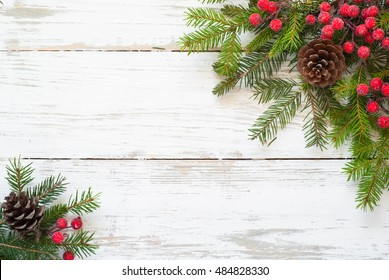 Christmas tree branch, decorations and gift box on white wooden table.