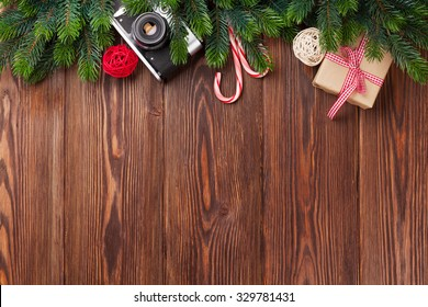 Christmas tree branch, gift box and camera on wooden table. Top view with copy space